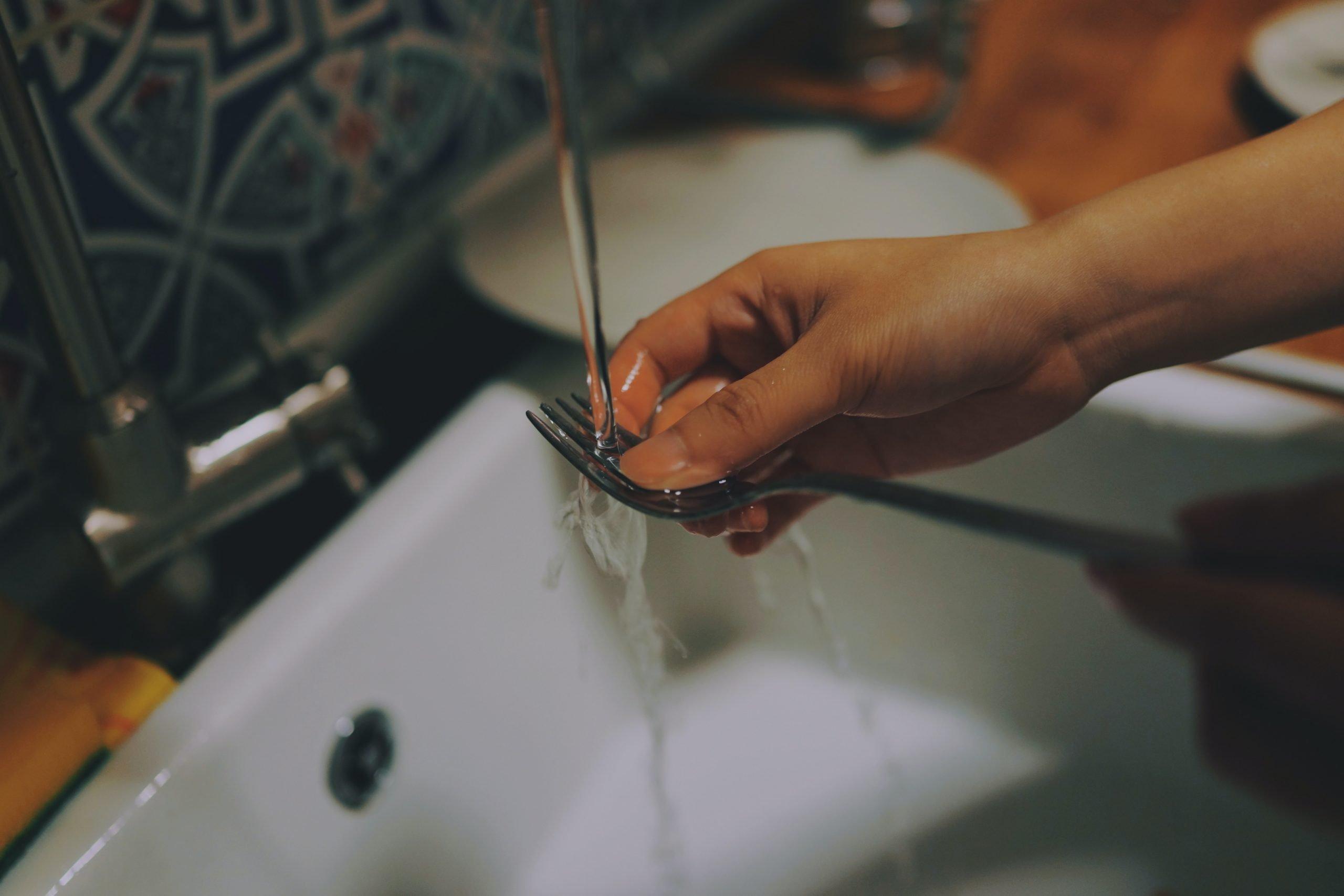 mano fregando un tenedor sobre fregadore