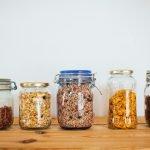 cinco envases de cristal para una compra cero residuo sobre una mesa de madera
